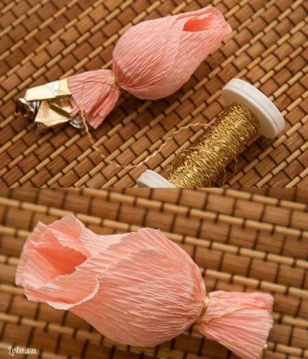 Gấp nhẹ 2 cánh hoa hai bên vào trong tạo thành hình hoa hồng vừa hé nụ, lấy sợi chỉ cột chặt bên dưới viên kẹo, cắt bỏ phần giấy gói kẹo thừa.