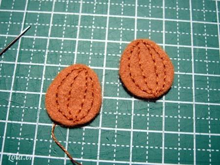 Bước 5: Tiếp theo là làm quả hạnh nhân: lấy 2 miếng vải nỉ màu nâu nhạt rồi cắt theo hình quả hạnh nhân rồi khâu theo đường dọc quả (các bạn chú ý chỉ khâu phải cùng màu với màu vải nỉ nhé).