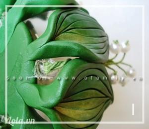Bước 5: Gắn cành hoa vào lọ: - Cắm chùm hoa xen vào giữa hai lá, cách hai lá lại cắm 1 chùm, uốn cong phần cuối chùm hoa ôm theo dáng lọ cắm nến, dùng keo dính chặt tại chỗ đó. - Uốn cho dáng chùm hoa ôm sát hài hòa theo thành lọ hoa.