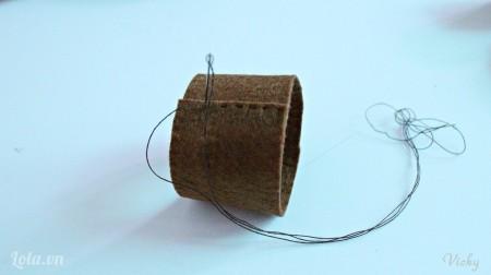 Cuộn tròn mảnh vải nỉ màu nâu và dùng kim may lại. Chú ý là đường vừa đủ để bọc xung quanh lõi khăn giấy nhé!