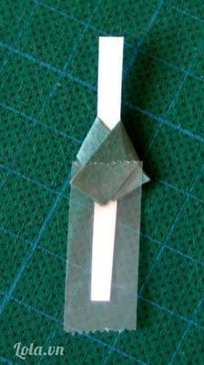 Cắt 1 tấm bìa nhỏ dài như hình làm thân cho búp bê rồi gấp 1 đoạn giấy màu xanh lá nhỏ qua làm cổ áo kimono.