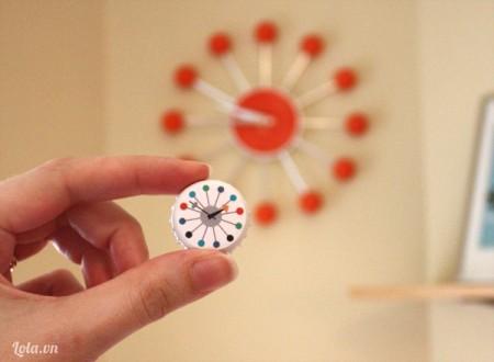 Bạn tải hình đồng hồ dễ thương về, in và cắt ra . Sau đó bôi keo sữa lên bề mặt nắp chai và dán mặt đồng hồ vừa tải lên .