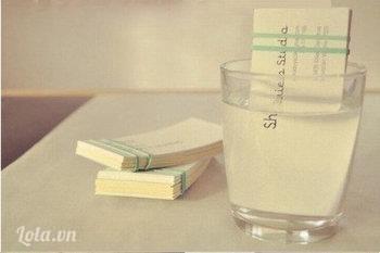 Cột chặt 1 đầu của namecard, ngâm 1/3 namecard vào nước trong ít phút.