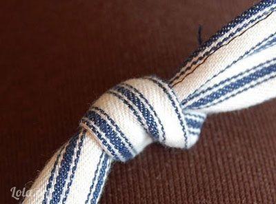 Rồi sau đó dùng 1 đoạn dây khác thắt nút ở giữa 2 miếng vài chồng lên nhau.