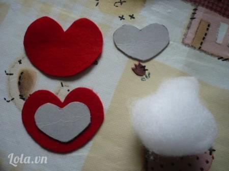 Đầu tiên các bạn lấy một miếng bài cứng và cắt làm hai hình trái tim. Các bạn có thể vẽ hình trái tim lên giấy bìa trước rồi mới cắt như thế hình trái tim của các bạn sẽ đẹp hơn. Sau đó các bạn dùng miếng vải nỉ, cũng cắt theo hình trái tim, nhưng các bạn lưu ý là hình trái tim ở vải có kích thước to hơn hình trái tim bằng giấy bìa nhé!