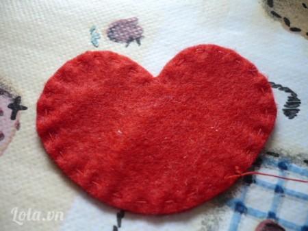 Sau khi đã cắt xong, các bạn lấy một hình trái tim bằng vải nỉ và dùng kim chỉ khâu xung quanh viền của hình trái tim, các bạn nhớ là chúng ta nên dùng chỉ cùng màu với hình trái tim, và các bạn chỉ xuyên chỉ vào thôi chứ đừng thắt nút nhé!