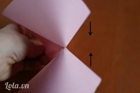 Nắm giấy giữ xuống theo đường ngang lại với nhau. Dùng tay chỉnh 2 phía giấy theo hình tam giác
