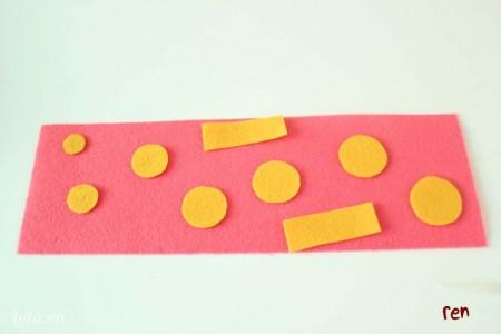 cắt vải nỉ màu hồng có kích thước phù hợp với cái ly,cắt thêm hình tròn và hình chữ nhật bằng vải nỉ màu vàng để trang trí