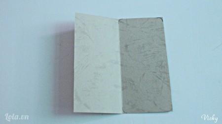 Cắt giấy bìa thành hình chữ nhật kích thước tùy ý. Sau đó gấp đôi mảnh giấy lại.