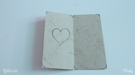 Dùng bút chì vẽ bo tròn các cạnh giấy, vẽ 1 trái tim ở giữa như hình bên.