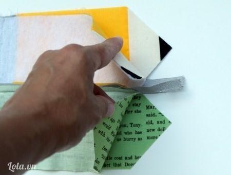 Lặt ngược mặt sau lại, để dây keo theo chiều đứng. Rồi lấy 2 tờ vải hình giấy báo qua một bên