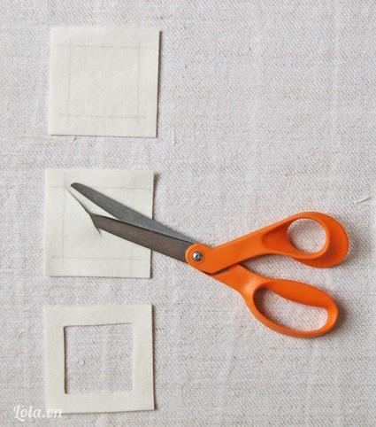 Dùng thước kẽ và bút kẽ hình vuông lên trên miếng vải nỉ. sau đó cắt bỏ hình vuông bên trong