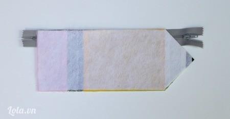 Lấy một bên mặt vải đặt lên trên dây kéo, lót thêm một miếng lớp keo lên trên cùng