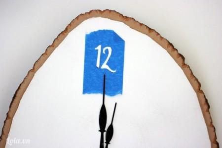 Kế tiếp bạn cắt con số 12 từ băng keo, rồi dán lên trên đầu của khúc gỗ