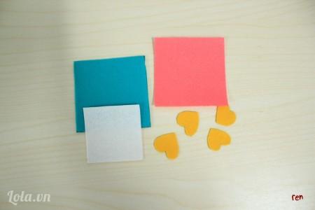 Cắt 2 hình vuông màu xanh và hồng kích thước 8x8cm, hình vuông màu trắng kích thước 6x6cm,và 4 hình trái tim để trang trí