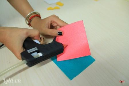 Dùng súng bắn keo dán 2 hình vuông hồng và xanh lại với nhau