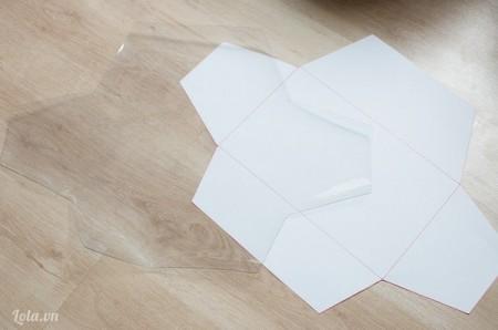 Vẽ mẫu lên giấy rồi cắt ra, sau đó đặt giấy lên miếng nhựa và cắt theo viền của mẫu giấy.