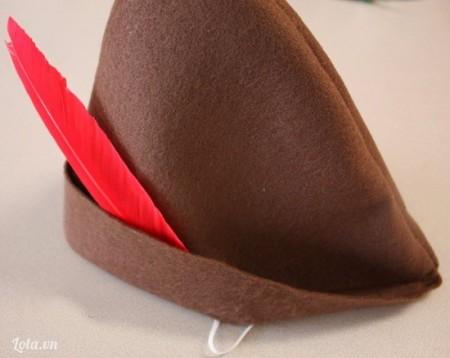 Đính thêm chiếc lông chim giả màu đỏ là bé đã có chiếc mũ Peter Pan đáng yêu.