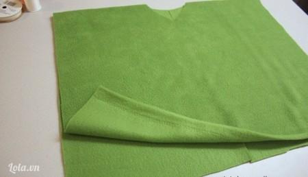 Gấp đôi miếng vải nỉ xanh lá may áo. Ở giữa nếp gấp, một bên bạn cắt một hình tam giác, một bên cắt hình vòng cung để làm cổ áo.