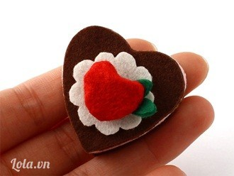 Dán hoa trắng lên trái tim nâu, gắn trái tim đỏ nhỏ xinh lên trên cùng còn lá xanh được gắn xen vào giữa hoa và trái tim nhỏ.
