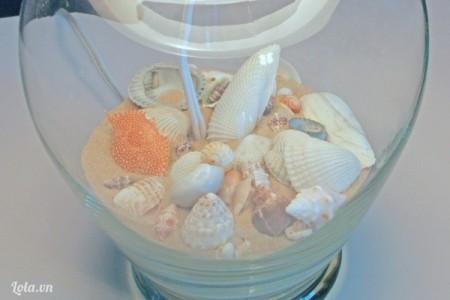 Kế dó bạn đổ cát vào bình, trang trí thêm vỏ xò, ốc biển lên trên nhé