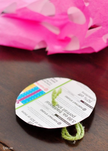 Dùng một tờ giấy cứng cắt vòng tròn rồi bạn đâm một lỗ tròn lên trên tờ giấy đó, lấy dây buộc làm dây treo, gắn thêm bóng đèn và dây đèn lên trên ( nếu bạn thích nhé )