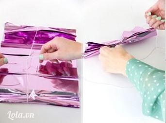 Mở tờ giấy ra, sau đó bạn thắt sợi dây lại ở giữa, từ từ để tờ giấy không bị nhàu. Vừa buộc vừa dùng tay xếp từng tờ theo chiều thẳng đứng lại với nhau. Tiếp tục bạn buộc chặt lại .