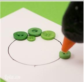 Bạn sắp xếp các nút áo xung quanh vòng tròn kiểu sắp xếp là tùy vào bạn sau khi đã ưng ý với tác phẩm của mình thì bạn dùng súng bắn keo dán cố định từng nút một lên bìa cứng