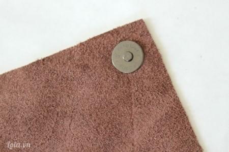 Bạn dùng búa đóng đinh tán để gắn nút đính cho túi xách