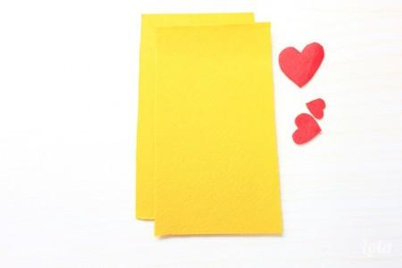cắt 2 mảnh vải dạ hình chữ nhật kích thước 7,5 x 14cm màu vàng để làm mặt trước và mặt sau của bao, cắt thêm 3 hình trái tim màu đỏ để trang trí