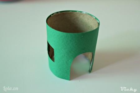 Cắt 1 mãnh giấy bìa cứng màu xanh. Cắt cửa và cửa sổ như phần lõi giấy, sau đó dán bao bọc xung quanh lõi giấy.
