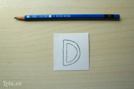 Dùng bút chì vẽ chữ cái lên giấy