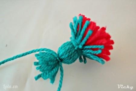 Tiếp tục quấn các sợi len xanh xung quanh đế hoa rồi dùng dây cột cố định.