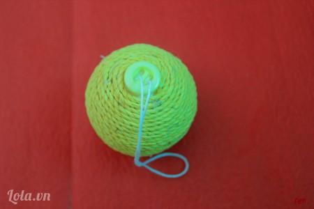 Dùng súng bắn keo dán nút lên đỉnh quả cầu
