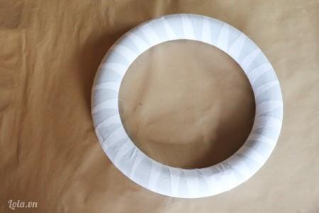 Dùng keo sửa đính một đầu vải, sau đó bạn quấn phủ kín khung tròn xốp