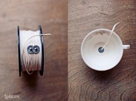 Bày những lọ đã chuẩn bị sẵn. Cột một đầu dây tim đèn vào thân bút chì, đầu kia cột vào mấu cố định dưới đáy tách. Nhớ trải một lớp giấy báo trên cả mặt bàn và sàn bếp, phòng trường hợp sáp bị đổ ra nhà.