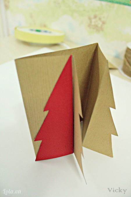 Dán 2 mảnh cây thông màu đỏ vào mép bìa bên ngoài thiệp như hình.