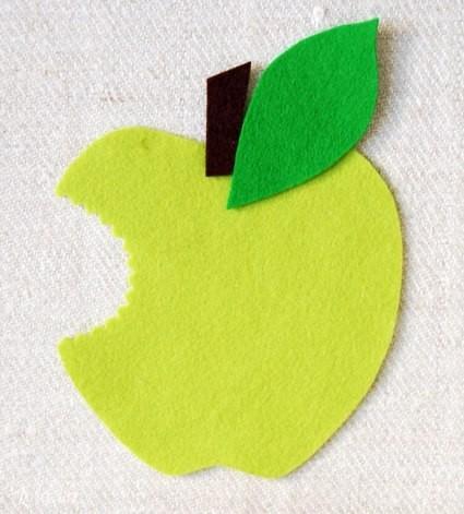Bây giờ, mình sẽ ốp nốt miếng vải xanh còn lại vào mặt sau quả táo, đồng thời dùng keo dán dính luôn cuống và lá cây vào như hình bên.