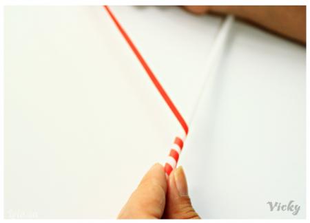Cắt các đoạn dây dài bằng giấy màu đỏ, rồi dùng keo dán quấn quanh ống hút.