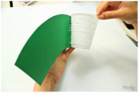 Bôi keo sữa khắp bề mặt ly nhựa rồi dán phần giấy xanh xung quanh nhé!