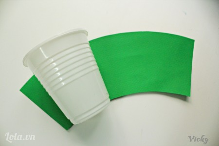 Đầu tiên chúng ta cắt 1 mảnh giấy cong theo chiều chiếc ly nhựa ( mách nhỏ là các bạn cứ lăn chiếc ly nhựa, rùi dùng bút vẽ theo đường lăn của ly thì sẽ nhanh hơn nhiều đó  )