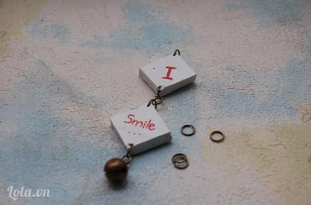 Dùng khoen tròn nối 2 miếng hình vuông vào với nhau, trang trí phí dưới bằng chuông đồng.