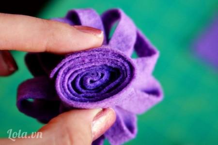 Giữ cho vải nỉ được thẳng rồi bạn từ từ cuộn từng miếng một lại với nhau cho đến khi ra hình bông hoa như thế này