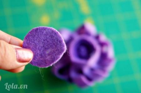 Cắt vòng tròn từ vải nỉ có kích thước bằng đáy của hoa. Dùng súng bắn keo dán vòng tròn lên mặt trên của đáy hoa