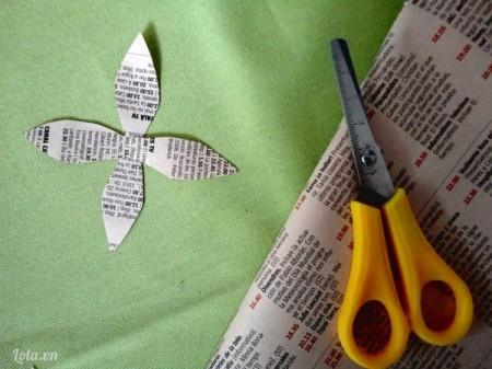 Cắt giấy báo thành hai cánh hoa để làm đài hoa