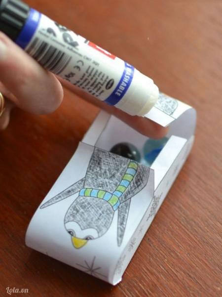 Dán keo lên mặt dưới của nữa hình còn lại và đặt dưới nữa hình trước, dùng tay giữ cho hai phần được dính sát vào nhau.