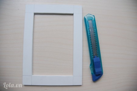 Cắt khung hình chữ nhật như trong hình kích thước 13x18 cm, đục lỗ ở giữa, khoảng cách từ mép ngoài tới mép trong là 2cm.